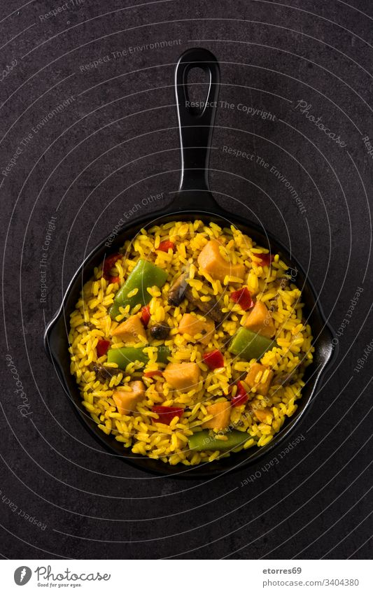 Fried rice with chicken and vegetables in frying pan on black background top view asian chinese cooked cuisine delicious dish food fried grain green meat