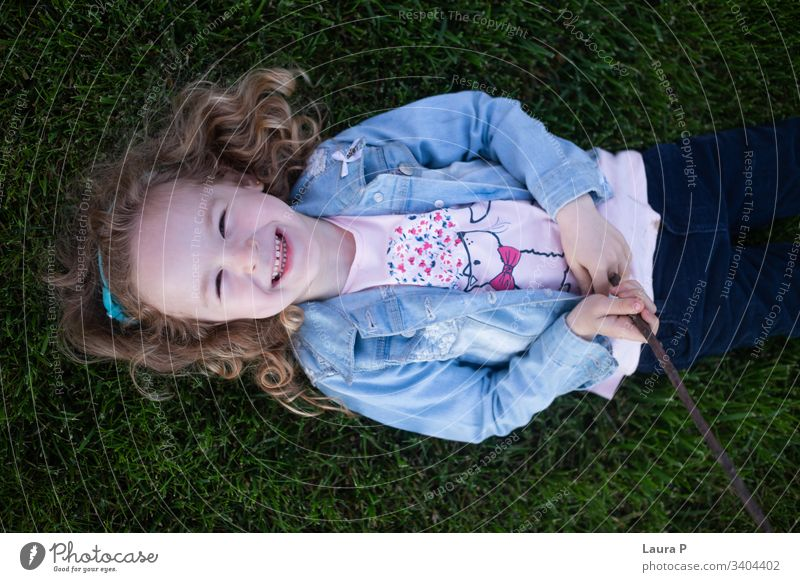 Beautiful blonde little girl laying on the grass, laughing - seen from above beautiful portrait child kid back green summer playing stick joy nature family time
