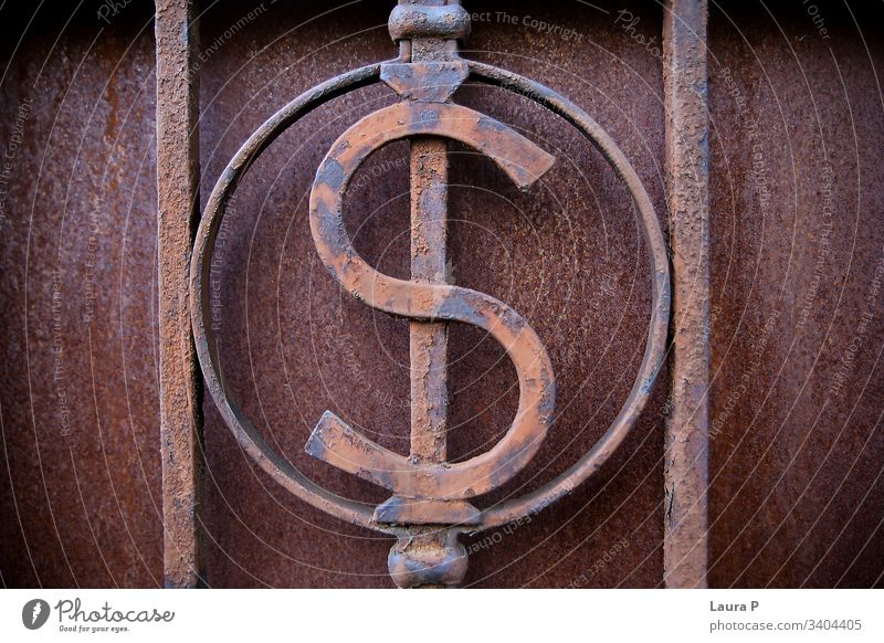 Close up of an iron $ dollar sign, decoration on a gate close up rusty grudge metal metallic old detail background iron bars