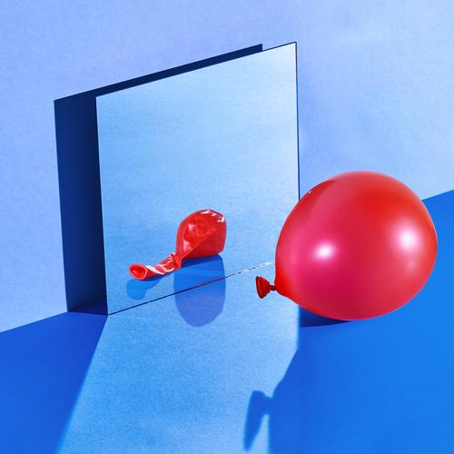 Still life space with a swollen balloon reflected on a deflated state blue still still life hard light mirror wall square squareformat cold empty no one noone