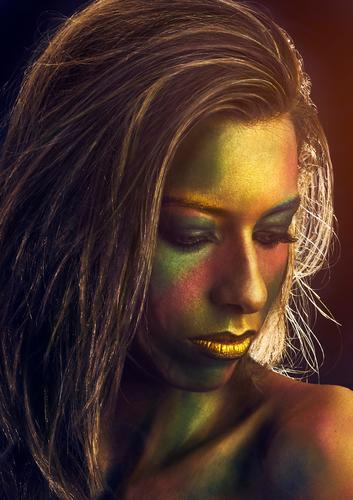 Portrait of a woman painted in gold Midas carnival halloween portrait hair vertical copy space female girl european caucasian people person face make up artist