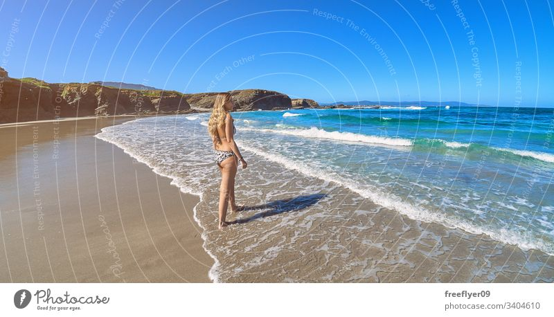 Young woman entering the ocean in a beach with cliffs in Galicia tourism hiking galicia spain ribadeo castros illas rock atlantic bay touristic cathedrals