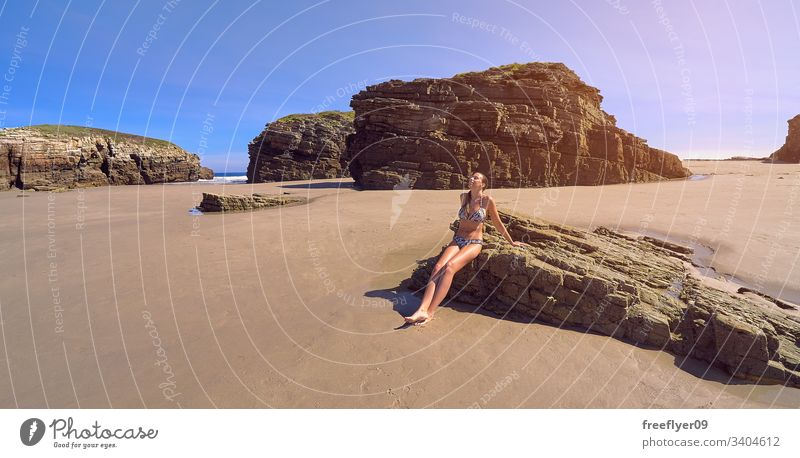 Young woman in bikini sitting on a rock on a beach full of cliffs tourism hiking galicia spain ribadeo castros illas atlantic bay touristic cathedrals ocean
