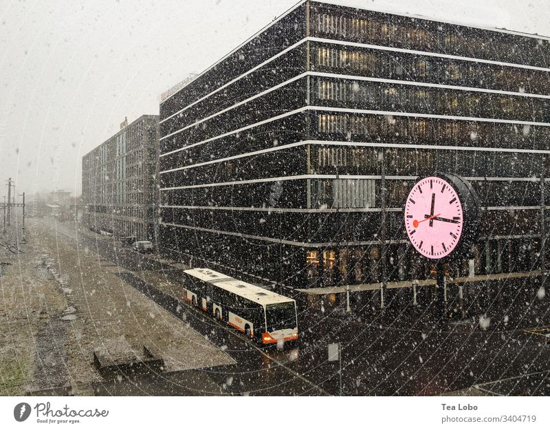 Clock in snow clock time Clock face Winter bus city blizzard hurry time change lack of time Exterior shot haste Digits and numbers lunch-time buildings offices