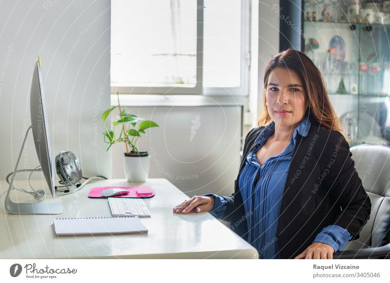 Executive woman in her office with large windows where the light enters. business businesswoman computer laptop young people sitting working desk smiling happy