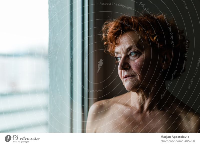 Mature woman by the window thinking about life adult age aged aging alone beautiful beauty care caucasian close-up closeup contemplating depression elder