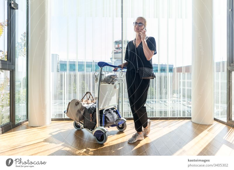 Casual woman on airport terminal talking on the cell phone, waiting for flight departure with luggage on trolley cart. travel international passenger tourist