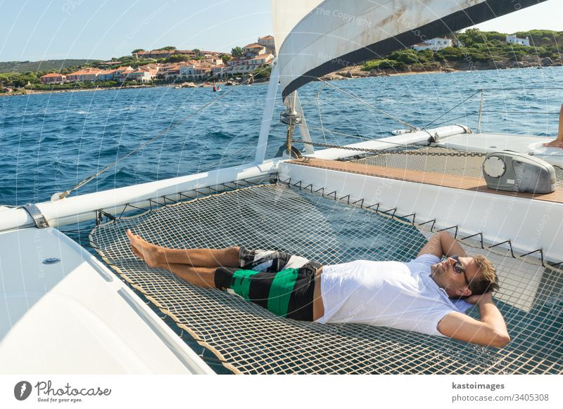 Sporty man relaxing, lying in hammock of a catamaran sailing boat on luxury nautic vacations near picture perfect Palau town, Sardinia, Italy. sea sailingboat