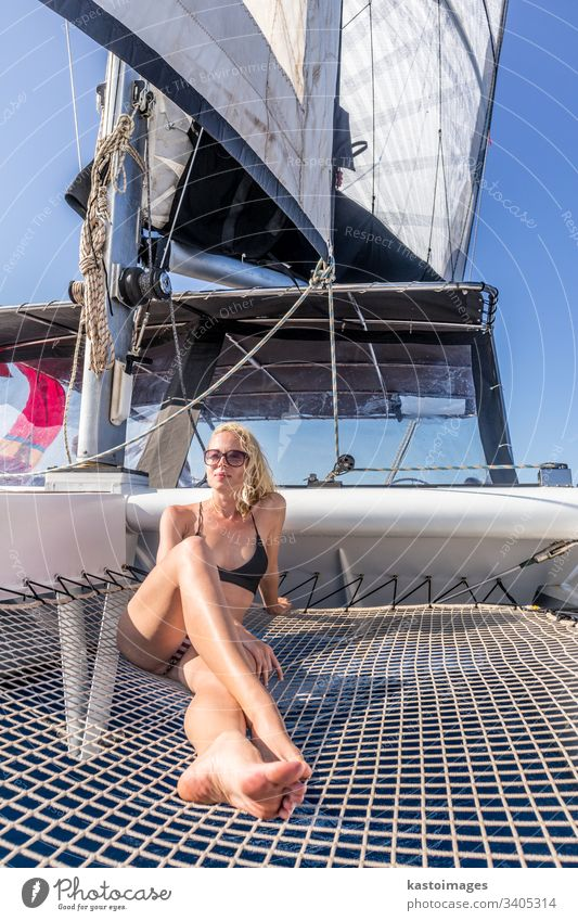 Woman relaxing on a summer sailing cruise, sitting on a luxury catamaran near picture perfect Palau town, Sardinia, Italy. woman boat sea sailingboat nautic