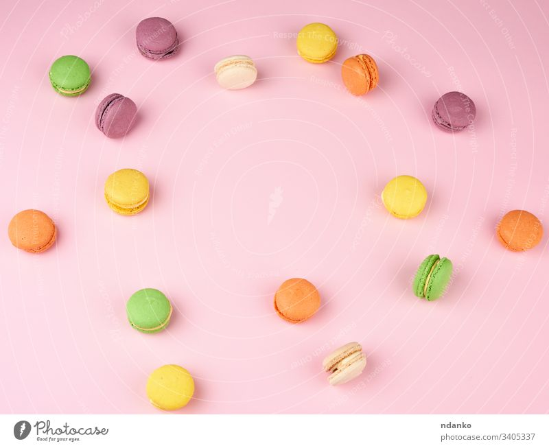 many multi-colored round baked macarons cakes on a light pink background almond assorted assortment bakery biscuit candy closeup colorful confection