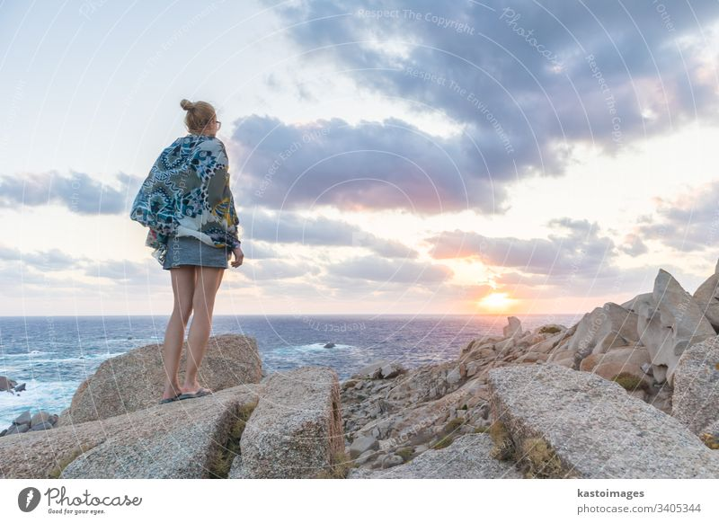 Solo young female traveler watches a beautiful sunset on spectacular rocks of Capo Testa, Sardinia, Italy. adventure lifestyle woman beach freedom landscape
