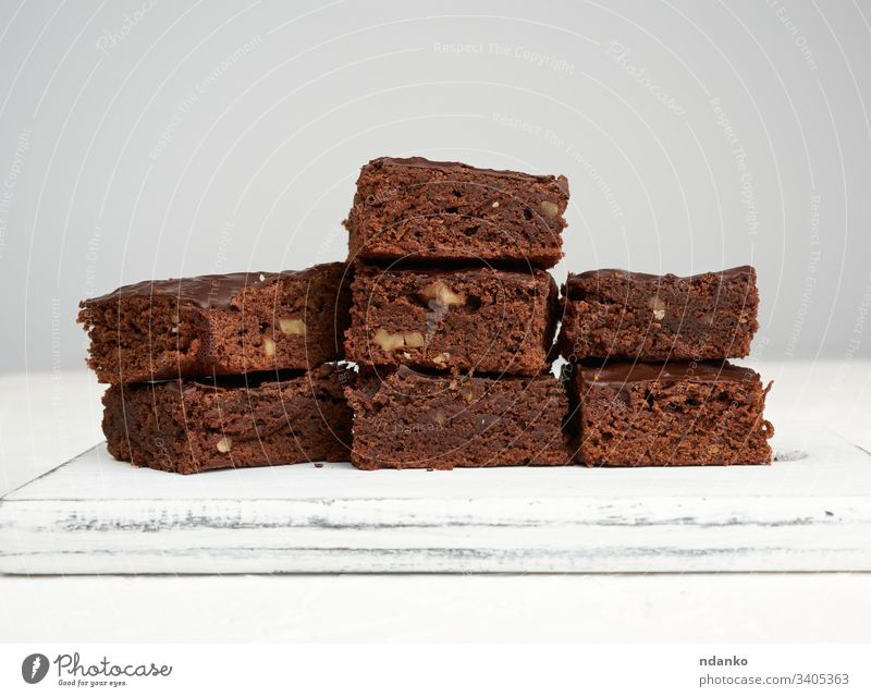 stack of square baked slices of brownie chocolate cake with walnuts bakery baking black closeup cocoa cooking cuisine dark delicious dessert eat food fresh