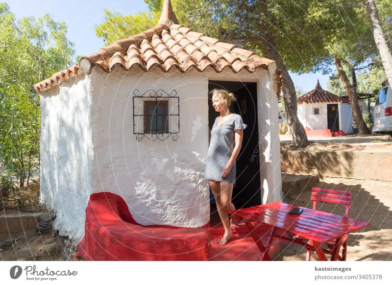 Woman enjoying relaxing summer vacations in authentic vintage bungalow of camping village under mediterranean pine trees, Palau, Sardinia, Italy. house woman