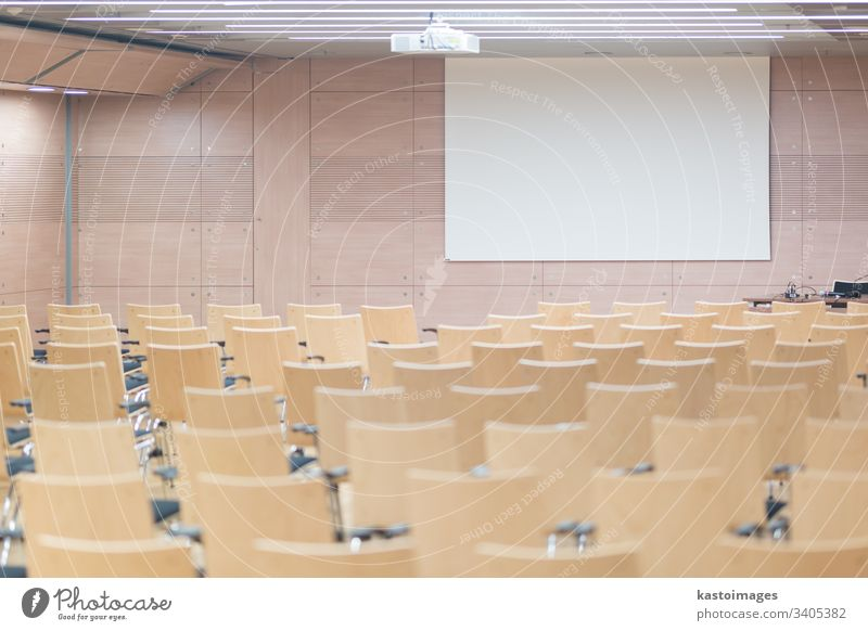 Empty wooden seats in a cotmporary lecture hall. auditorium education empty conference meeting presentation room chairs school white screen study university