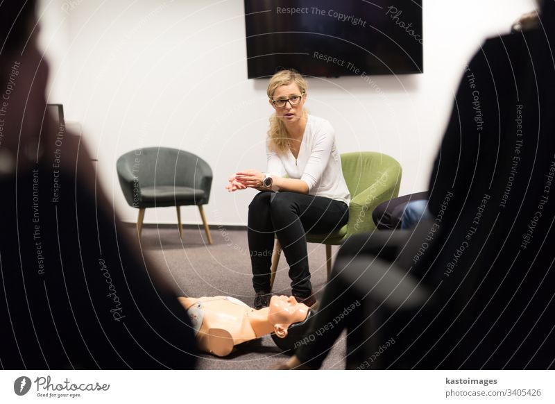 Instructor teaching first aid cardiopulmonary resuscitation course and use of automated external defibrillator on CPR workshop. training aed arrest attack