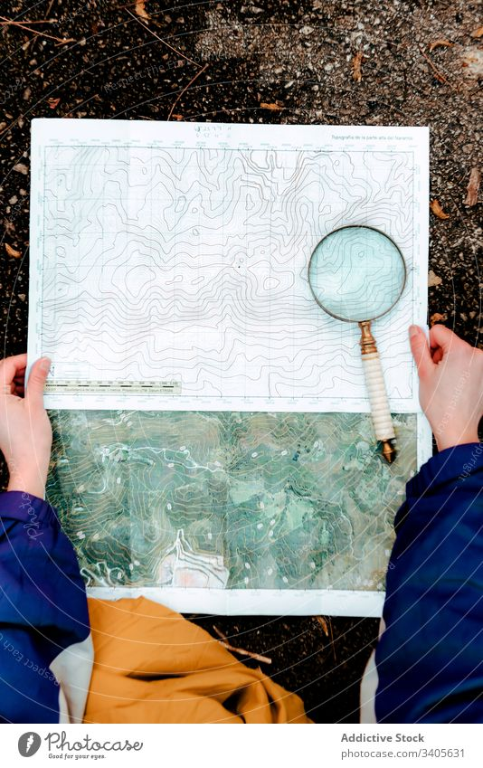 Unrecognizable hiker navigating with map and compass in countryside navigate traveler check topographic map magnifying glass ground equipment cartography tool