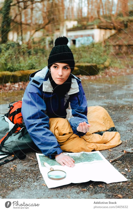 Hiker navigating with map and compass in countryside hiker navigate traveler check topographic map magnifying glass ground equipment cartography tool
