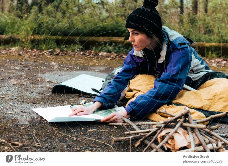 Focused young female hiker orientating on map in camp orientate woman backpacker search location trekking autumn navigate traveler check countryside equipment