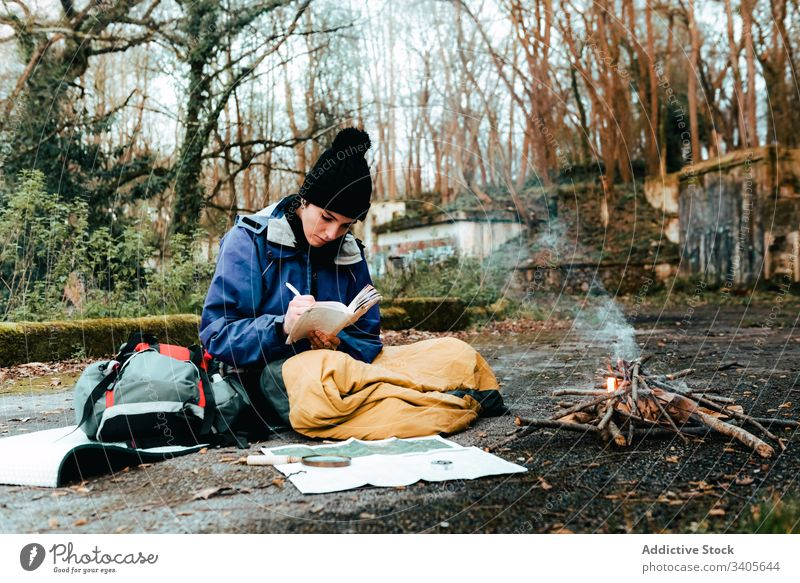 Young female backpacker making notes at campfire woman hiker write information trekking route rest bonfire countryside autumn nature environment adventure