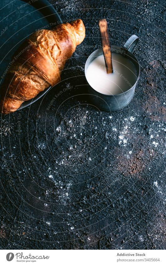 Croissant and milk on table croissant breakfast morning rustic mug fresh food cuisine pastry bun rough messy dirty homemade yummy gourmet meal organic baked