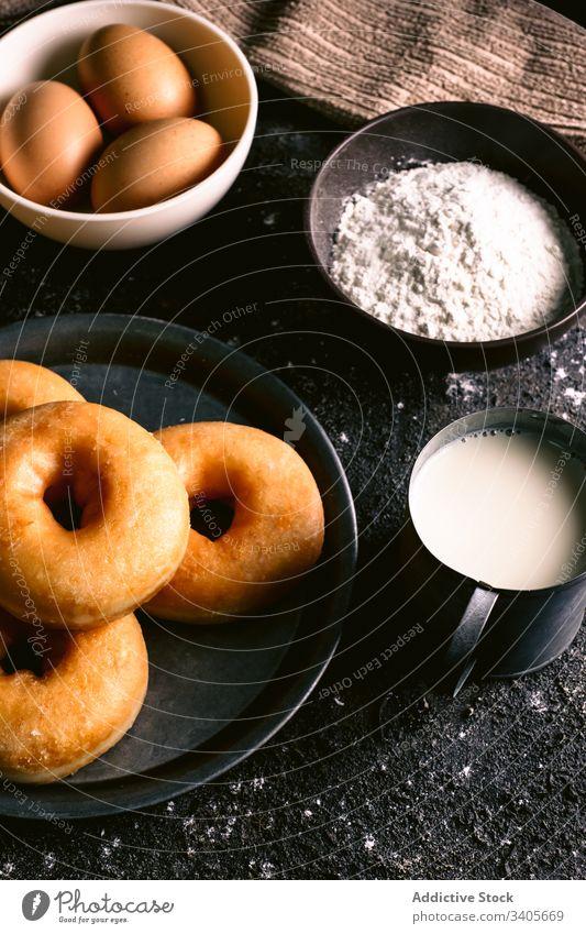 Doughnuts near ingredients on table doughnut cook kitchen recipe flour milk egg utensil pastry food napkin spoon tasty delicious bakery fresh sweet dessert