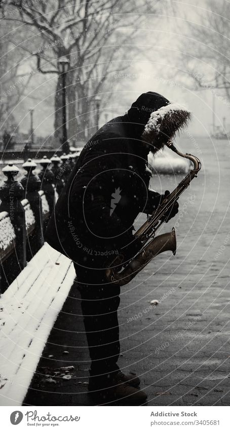 Anonymous man with saxophone at city street play winter modern jacket music melody sound instrument male entertain lifestyle season new york park harmony