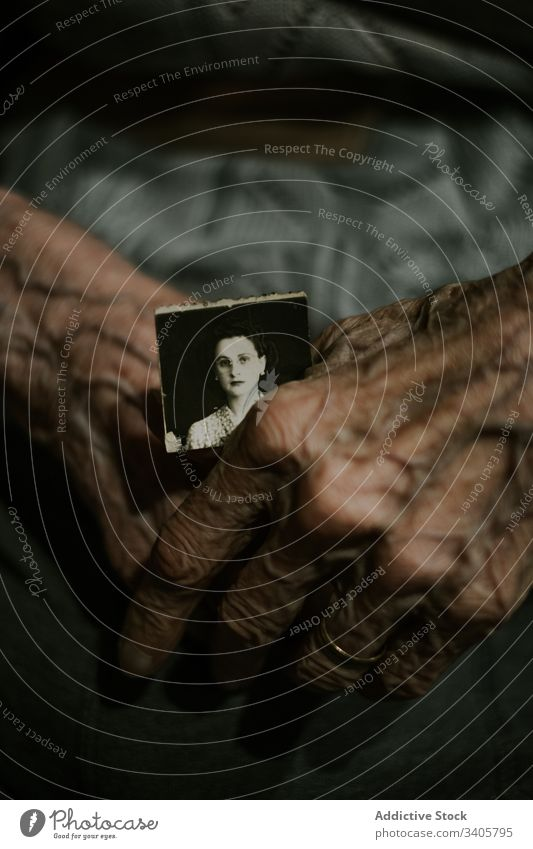 Unrecognizable senior person with old photo elderly memory remember retire dark nostalgia tranquil picture image paper aged mature pensioner wrinkle examine