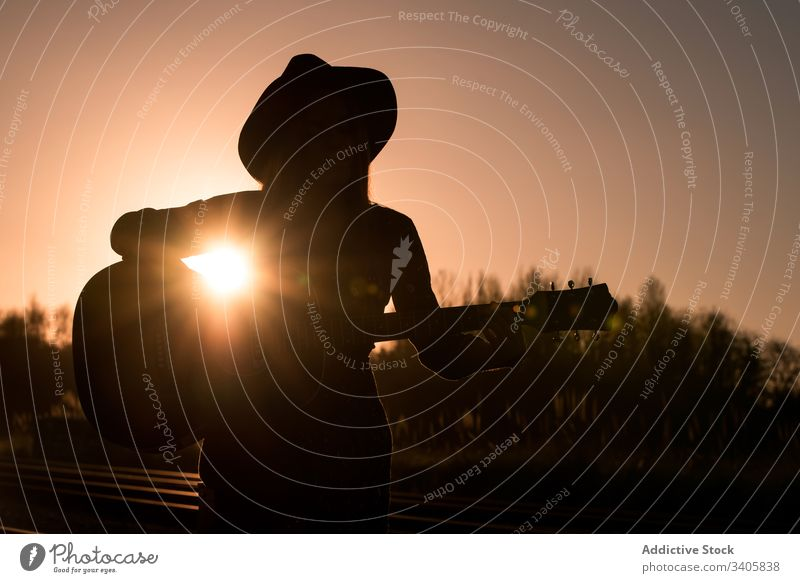 Woman playing guitar on rails woman music travel style perform countryside female instrument acoustic musician song entertain hat boho sound melody lifestyle