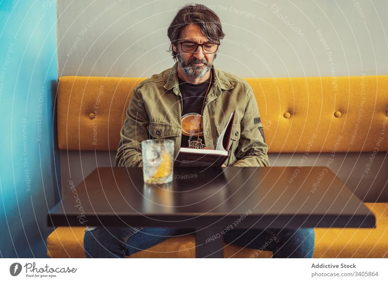 Bearded man reading book in cafe sofa table cocktail serious sit male casual modern lifestyle mature adult relax rest bar drink beverage smart glasses guy story