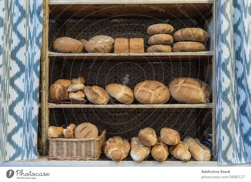 Fresh bread on shelves in bakery shelf sell assorted fresh food rustic loaf pastry baked organic arrangement natural tasty delicious gourmet composition curtain