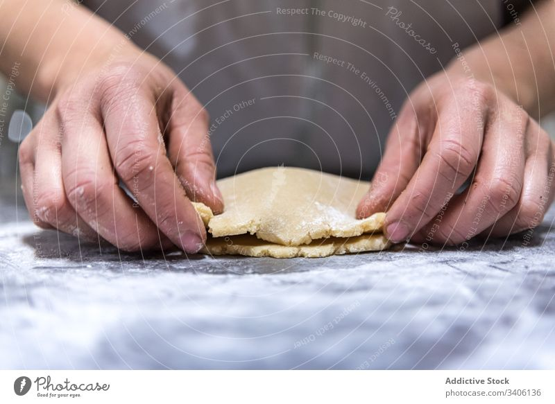 Crop baker rolling jam into dough cook pastry table flour bakery work chef kitchen food prepare fresh cuisine ingredient recipe occupation job small business