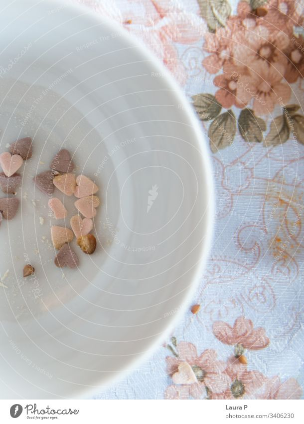 Heart shaped sweets in a white, round bowl, on a vintage table cloth hearts heart-shaped pink purple shabby chic floral flowers close-up concept decor
