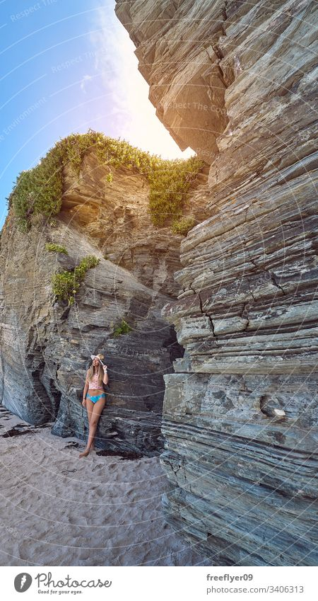 Young woman contemplating a cave made of rocks in Galicia, Spain tourism hiking galicia spain ribadeo castros illas atlantic bay touristic cathedrals cliff