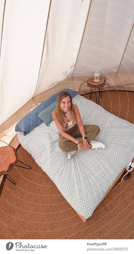 Young woman on the interior of a camping tent tourism hiking glamping big site vacation outdoor comfort sheets beautiful comfortable summer inside resort