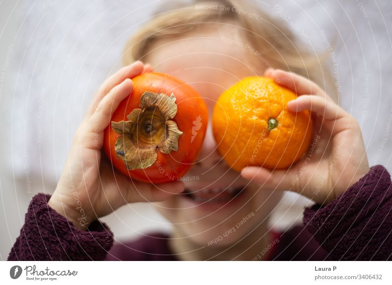 Little girl holding a kiwi and an orange in front of her eyes, laughing cute little child kid playing fun smiling fruits hands hiding hiding behind