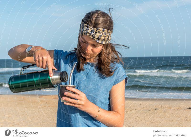 Young woman on beach with mate tea person feminine Beach Sand Waves Water Ocean Mate tea Thermos coffee pot windy Headband Summer Beautiful weather Sky Horizon