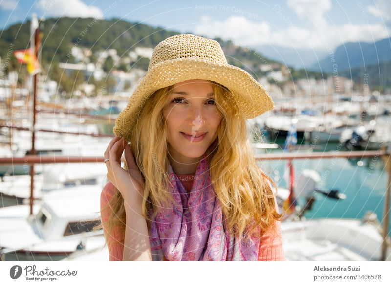 Portrait of young woman with light curly hair in straw hat enjoying sun and breeze, smiling. Sunny harbor with boats and yachts, green mountains on background. Enjoying life, happy person traveling,