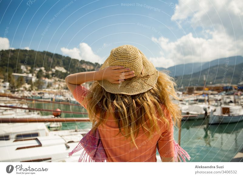 Portrait of woman with light curly hair, rear view,  holding straw hat with hand. Sunny harbor, boats and yachts, green mountains on background. Enjoying life, happy traveling,