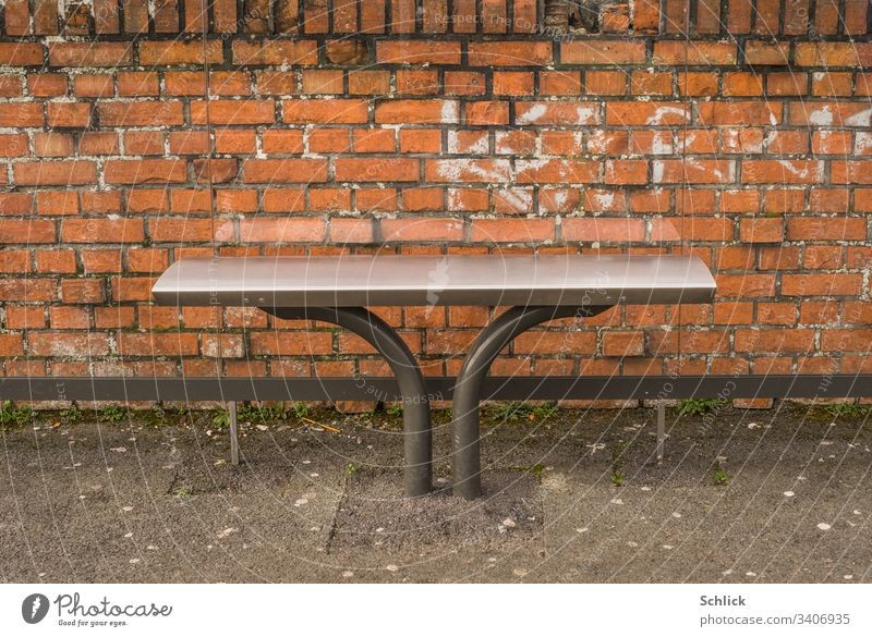 Bus stop modern stainless steel bench in front of brick wall and old chewing gum on the asphalt detail Bench seating furniture Asphalt Chewing gum Modern Old
