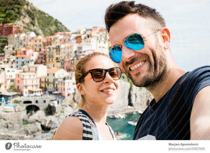 Young couple taking a selfie in Manarola, Cinque Terre in Italy adults boyfriend camera cityscape coast colorful europe fun girl girlfriend happiness happy