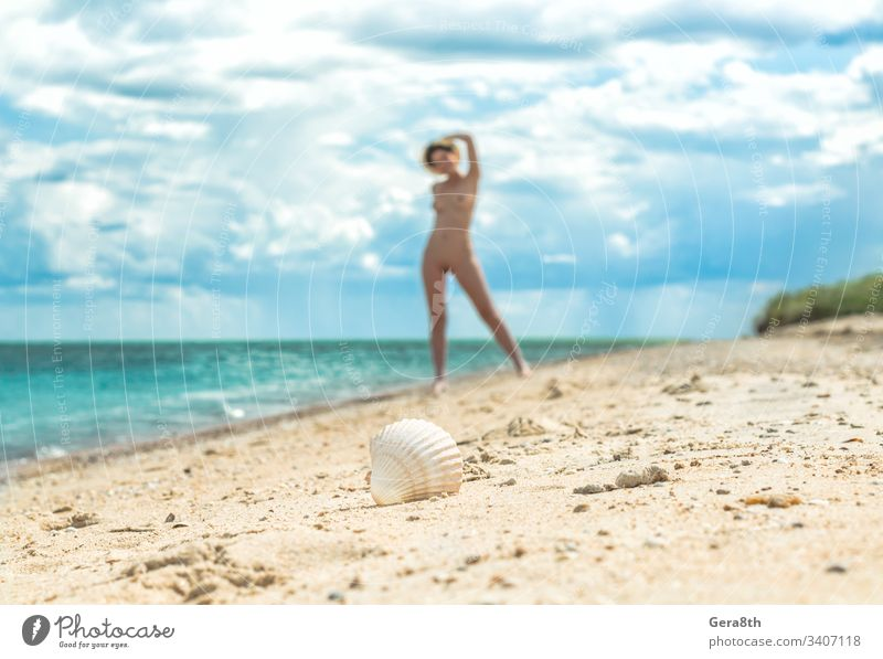 young nude girl with a hat walks on an empty beach near the sea surf against the blue sky with clouds in summer alone blur body climate day erotic female figure