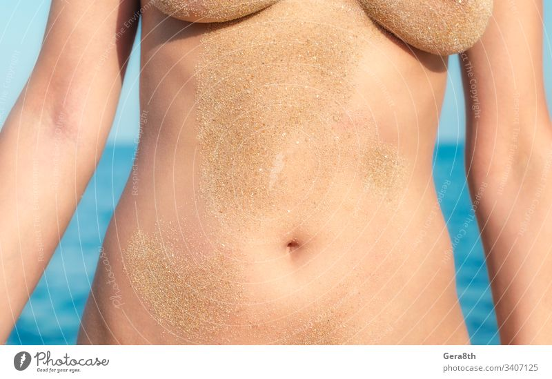 beach sand on a naked female body on the background of the sea close up adult belly blue breasts close-up color day freedom girl grains of sand hands health