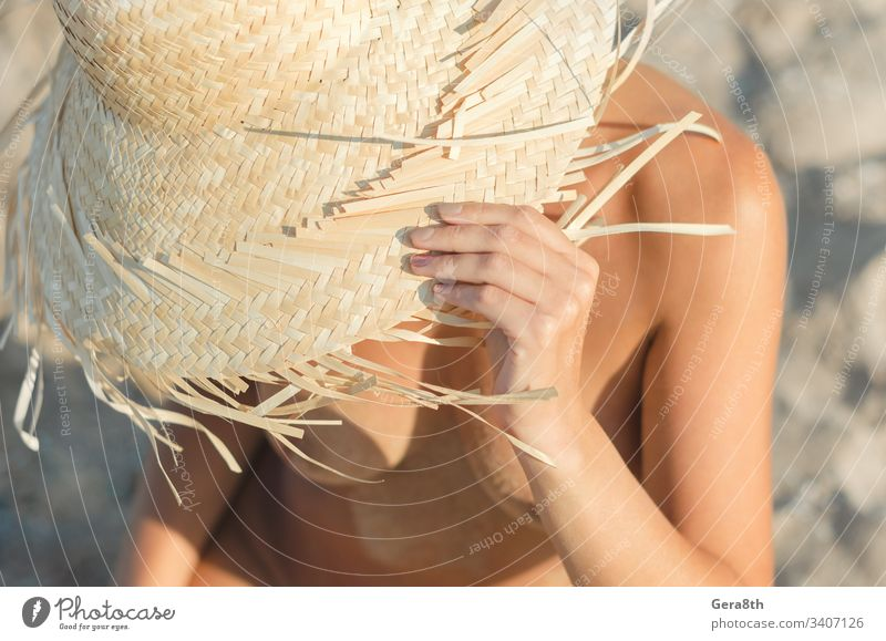 young girl in a straw hat sits on the sand at the beach close up body climate closeup day female female body fingers freedom hands head hide hot naked nature