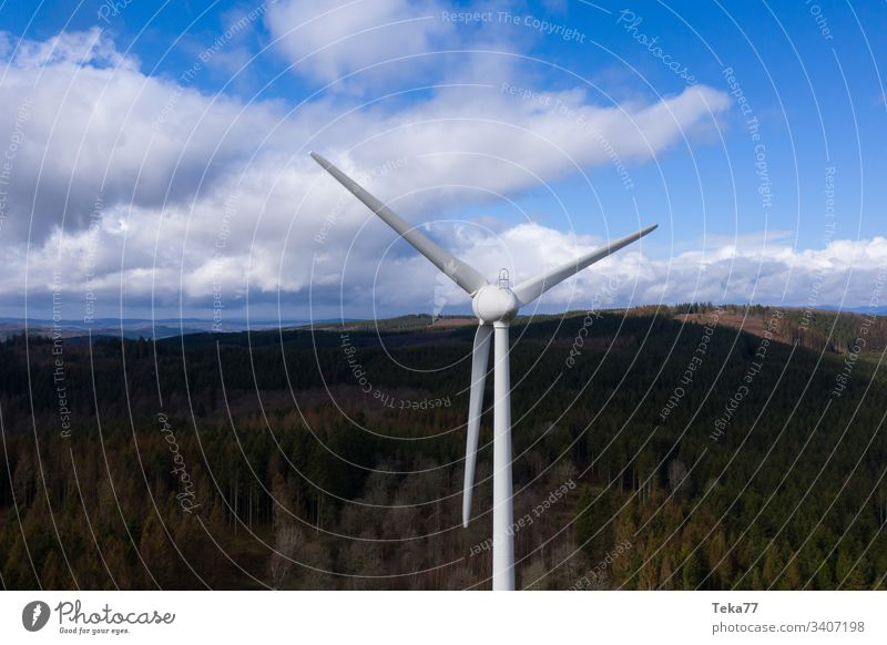 wind wheel in front a dark forest hills landscape and cloudscape air bright cloudscapes electricity energy from above green electricity green energy turbine