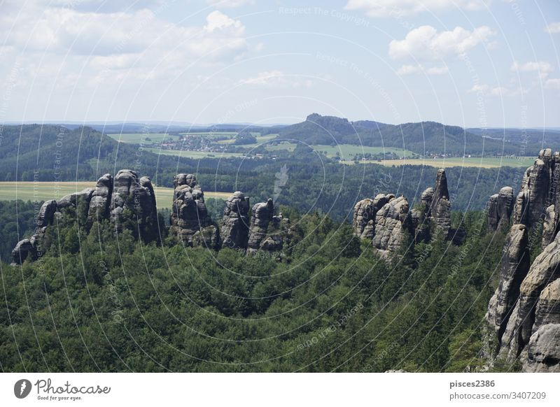 View over the Schrammsteine area and the landscape of Saxon Switzerland climbing clouds journey rocky sandstone switzerland woods blue blue sky cliff