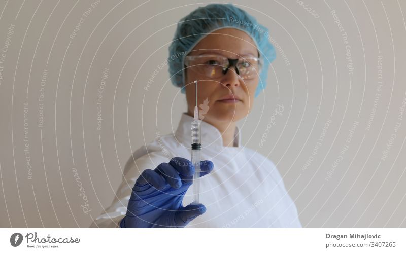 Female doctor holding a injection in hand anesthetic antibiotic arm asian woman biology care chinese clinic close-up closeup coronavirus dose drug equipment