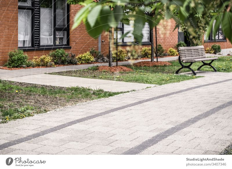Paved path leading to a modern brick building house pavement paved clean stone tile window windows spring summer tree trees leaves leaf living lifestyle facade