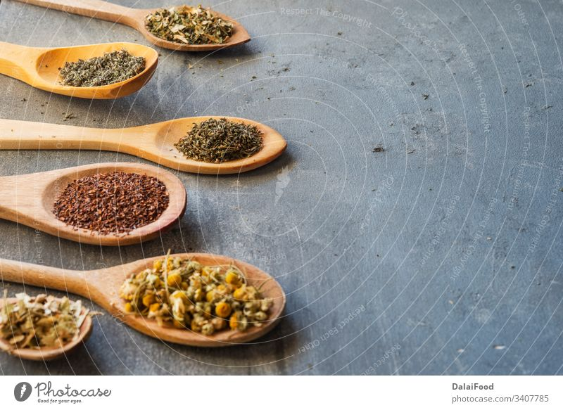 herbs with wooden spoon in gray slate background anisetree aroma aromatherapy bio camomile chili close up copy spacs curcuma ecologic green green tea herbal