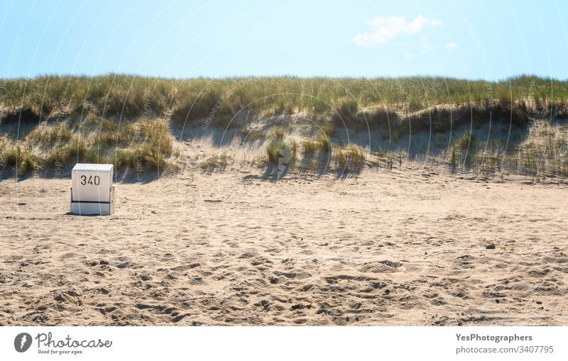Beach scenery with a single wicker chair in the morning light alone beach coast coastline dunes europe grass heat island korb landmark landscape marram minimal