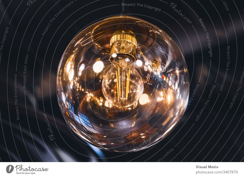 Giant vintage style light bulb with its retro filaments visible inside color shallow depth of field closeup close-up artificial light nobody no people abstract